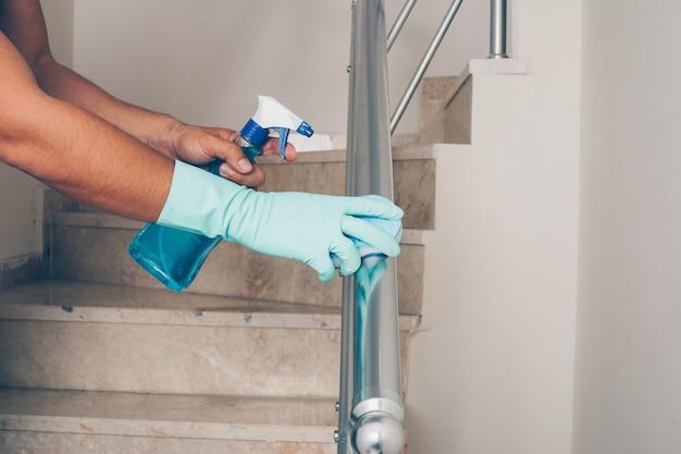 Ritratto di un corrimano della scala di pulizia dell'uomo in guanti