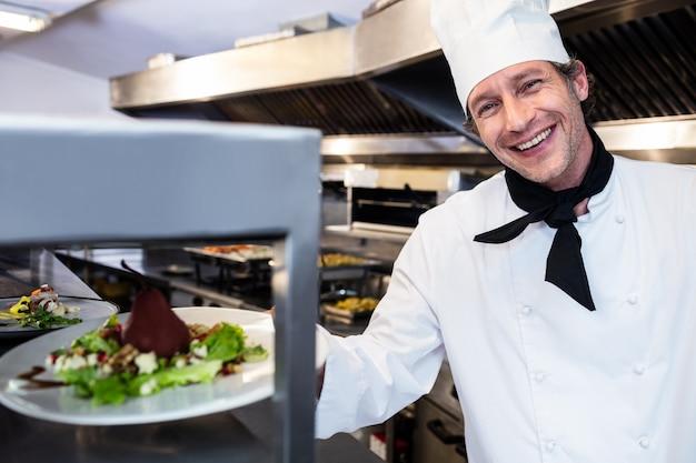 Ritratto di un cuoco unico che passa il piatto di cena attraverso la stazione di ordine