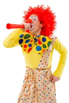 Ritratto di un divertente clown giocoso in parrucca rossa che soffia il corno.