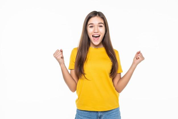 Ritratto di un'eccitata giovane donna che celebra il successo sul muro bianco