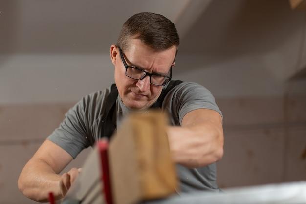 Ritratto di un falegname maschio al lavoro nel negozio di un falegname.