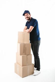 Ritratto di un fattorino felice che posa con la pila di scatole di cartone