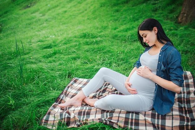 Ritratto di un felice capelli neri e orgogliosa donna incinta in una città nel parco. foto del modello femminile che tocca la sua pancia con le mani. il modello femminile è seduto sull'erba.