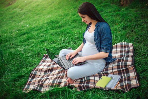 Ritratto di un felice capelli neri e orgogliosa donna incinta nel parco. il modello femminile è seduto sull'erba e sta lavorando al computer