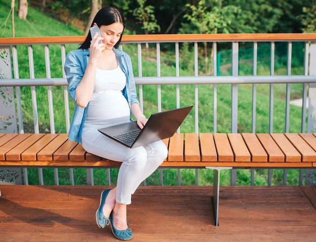 Ritratto di un felice capelli neri e orgogliosa donna incinta nel parco. il modello femminile funziona sul computer