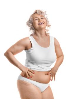 Ritratto di un felice ridendo di mezza età plus size modello in lingerie bianca.
