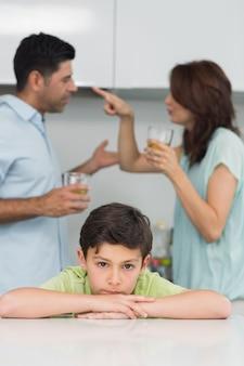 Ritratto di un figlio triste mentre i genitori litigano