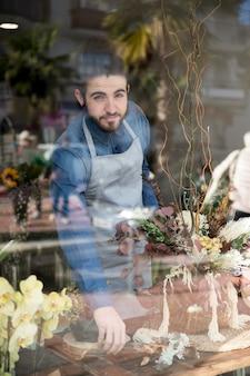 Ritratto di un fiorista maschio che sta dietro il vetro che sistema il fiore nel suo negozio