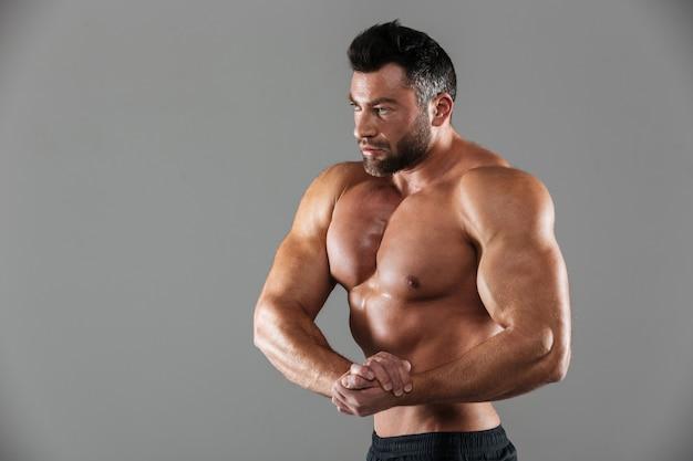 Ritratto di un forte culturista maschio senza camicia muscolare