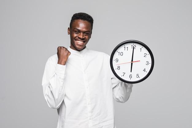 Ritratto di un gesto afroamericano di vittoria dell'orologio di parete della tenuta dell'uomo isolato su un fondo bianco