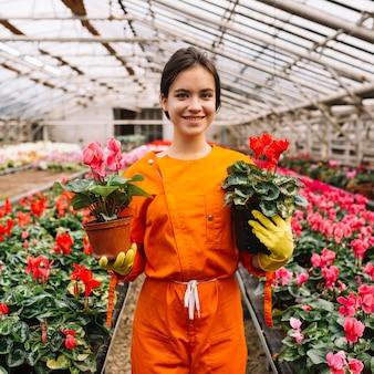 Ritratto di un giardiniere femminile felice che tiene i vasi da fiori rosa e rossi di ciclamino