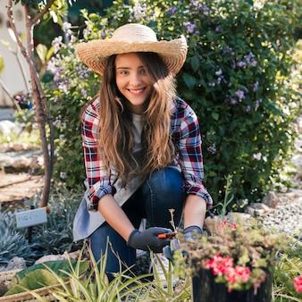 Ritratto di un giardiniere femminile sorridente che porta cappello che taglia le piante nel giardino