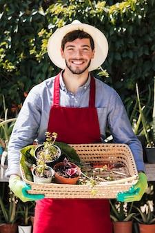 Ritratto di un giardiniere maschio sorridente che tiene le piante in vaso nel canestro