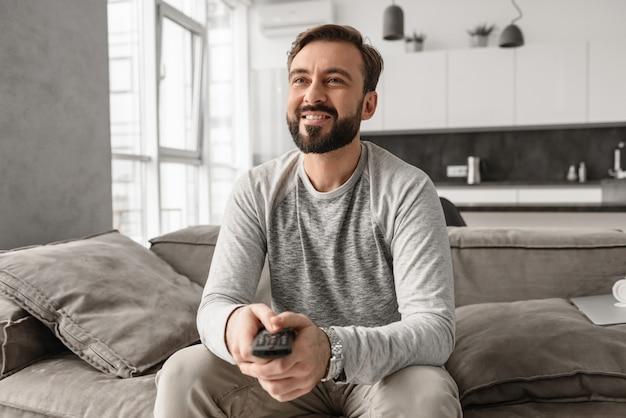 Ritratto di un giovane allegro che tiene il telecomando della tv