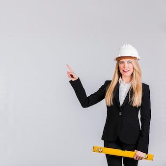 Ritratto di un giovane architetto femminile che indossa l'elmetto protettivo che indica la sua barretta contro la priorità bassa grigia