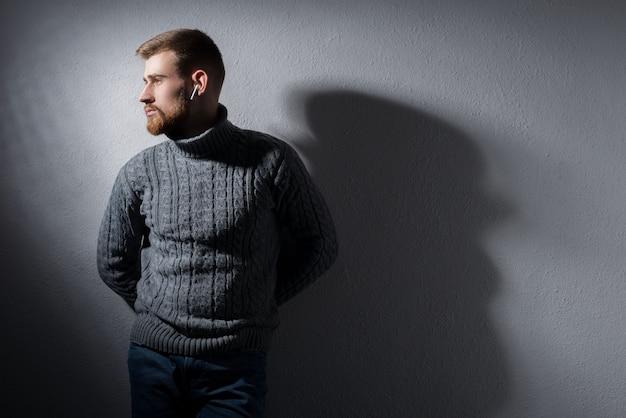 Ritratto di un giovane barbuto di venticinque anni. in un caldo maglione invernale, fiero, grigio, distoglie lo sguardo.