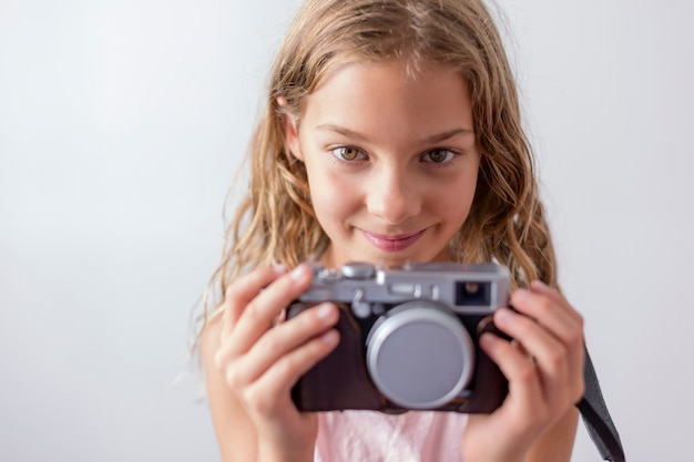 Ritratto di un giovane bel bambino in possesso di una macchina fotografica d'epoca e sorridente. sfondo bianco. bambini al chiuso. concetto di fotografia