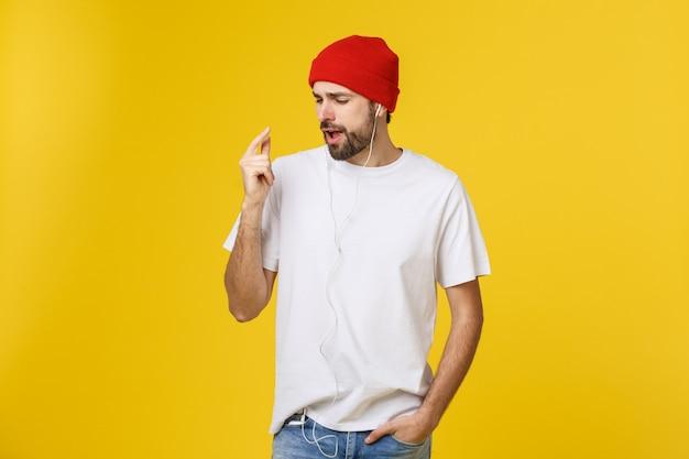 Ritratto di un giovane bello ballare e ascoltare musica, isolato su giallo