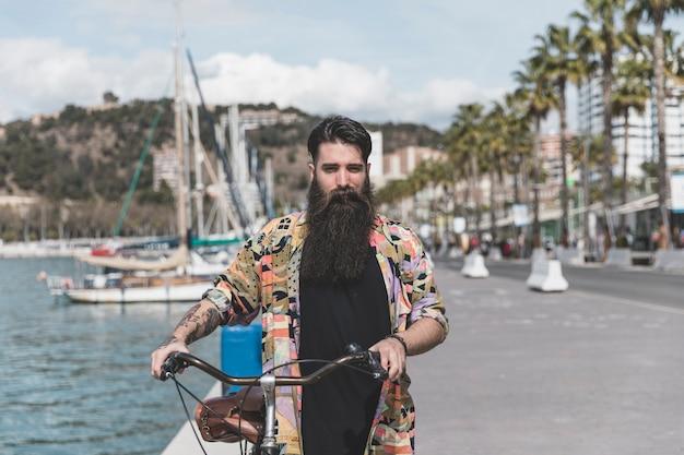 Ritratto di un giovane che cammina con la bicicletta vicino alla costa