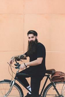 Ritratto di un giovane che si siede sulla bicicletta che guarda l'obbiettivo contro il muro beige
