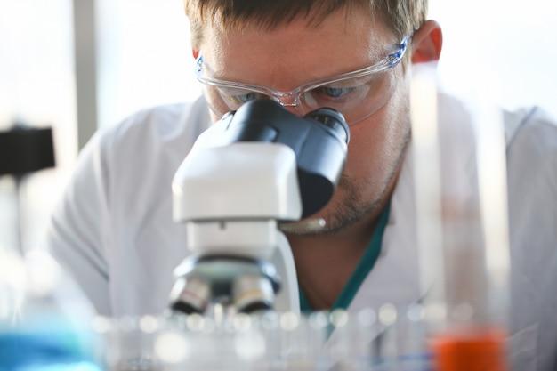 Ritratto di un giovane chimico che osserva in binocolo