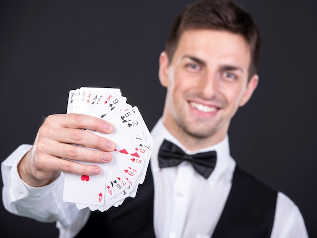 Ritratto di un giovane commerciante sorridente con carte da gioco.