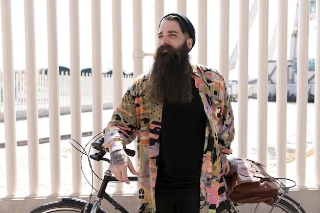 Ritratto di un giovane con la barba lunga che sta con la bicicletta davanti al recinto