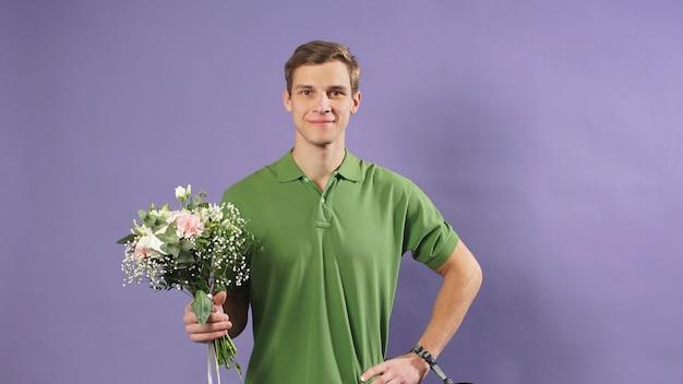 Ritratto di un giovane corriere con fiori nelle sue mani su uno sfondo isolato, servizio di consegna espresso