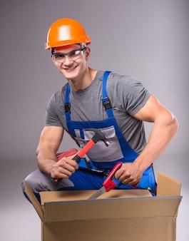 Ritratto di un giovane costruttore con strumenti in mano per costruire.