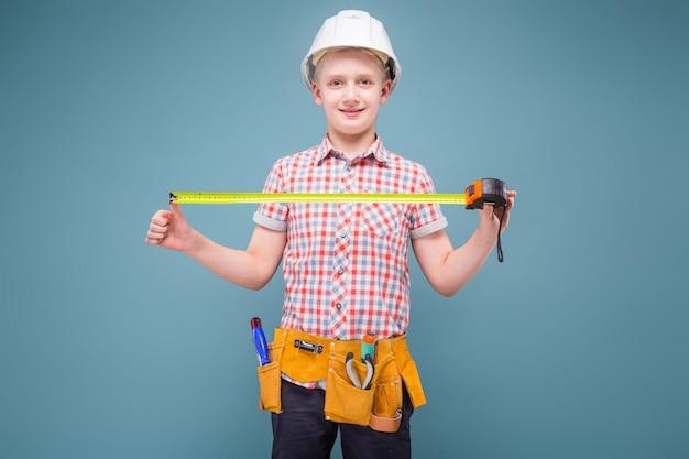 Ritratto di un giovane costruttore in un casco e un metro a nastro in mano