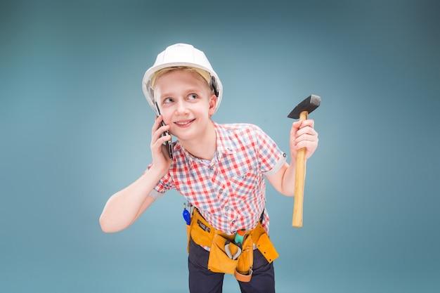 Ritratto di un giovane costruttore in un casco e una misura di nastro in mano