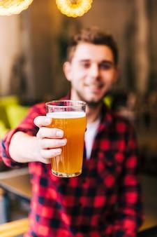 Ritratto di un giovane defocussed che tiene vetro di birra