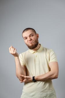 Ritratto di un giovane dispiaciuto in una maglietta gialla su grigio.