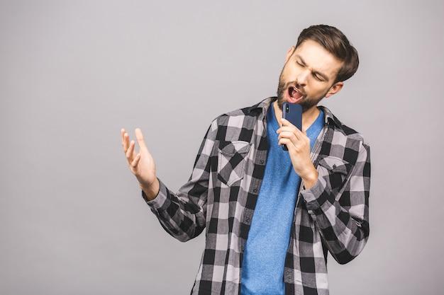 Ritratto di un giovane eccitato in t-shirt isolato sul muro grigio, tenendo il telefono cellulare schermo vuoto, cantando.