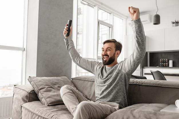 Ritratto di un giovane eccitato tenendo il telecomando della tv