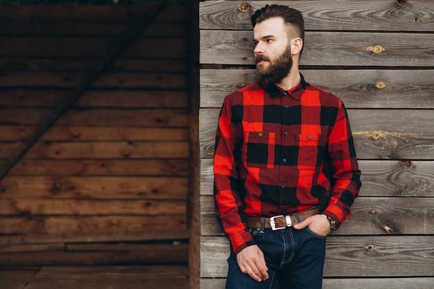 Ritratto di un giovane elegante uomo barbuto vestito in jeans e un vero lavoratore nero dalla camicia rossa.