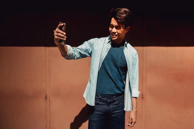 Ritratto di un giovane felice che sorride mentre usando telefono cellulare per prendere selfie.