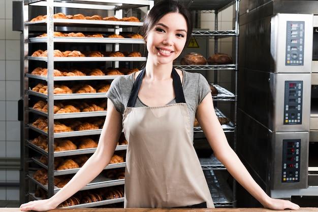Ritratto di un giovane fornaio femminile fiducioso in piedi davanti a scaffali di croissant al forno