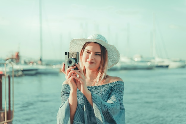 Ritratto di un giovane fotografo donna bionda in un abito e cappello con una fotocamera retrò all'aperto in spiaggia