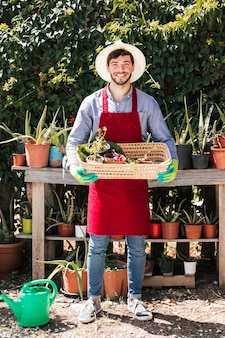 Ritratto di un giovane giardiniere maschio felice che tiene le piante in vaso nel canestro