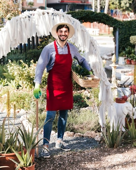Ritratto di un giovane giardiniere maschio sorridente che tiene strumento e canestro di giardinaggio