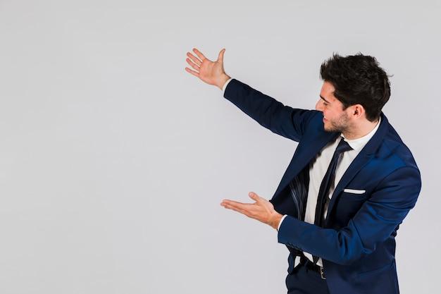 Ritratto di un giovane imprenditore che presenta qualcosa contro sfondo grigio