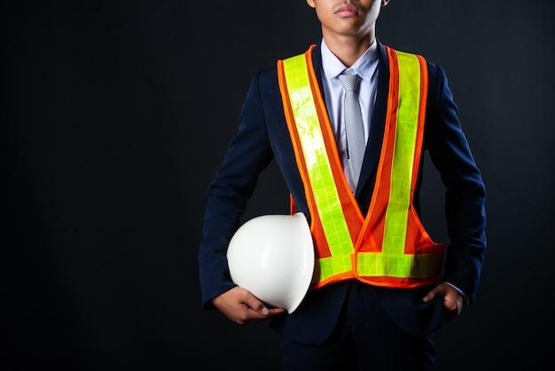 Ritratto di un giovane ingegnere allegro del cantiere dell'uomo d'affari, fine su.