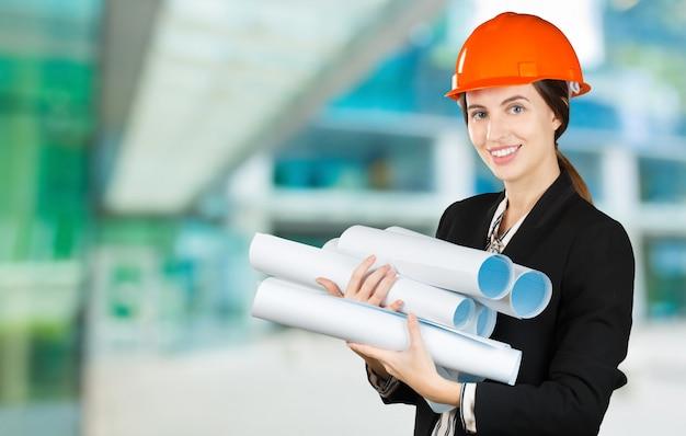 Ritratto di un giovane ingegnere femmina che indossa un casco di sicurezza sul luogo di lavoro