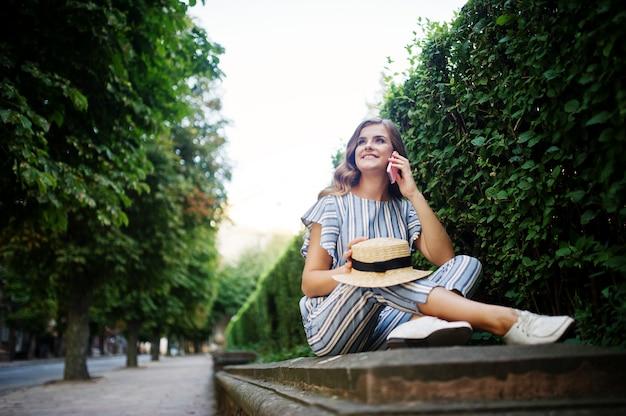 Ritratto di un giovane modello stupefacente nella seduta generale a strisce nel parco e parlando al telefono.