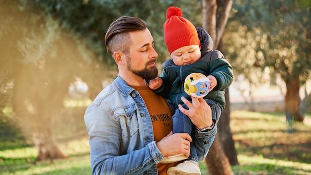 Ritratto di un giovane padre felice tenendo il figlio piccolo nelle mani
