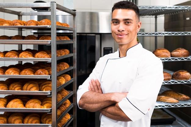 Ritratto di un giovane panettiere fiducioso maschio davanti a scaffali di croissant al forno