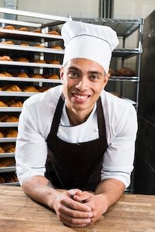 Ritratto di un giovane panettiere maschio sorridente in uniforme che si appoggia sul tavolo nel forno