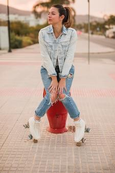 Ritratto di un giovane pattinatore femminile seduto sul marciapiede