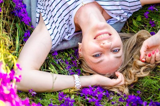 Ritratto di un giovane primo piano ragazza bionda caucasica. la ragazza giace sull'erba in una giornata estiva in un campo di bellissimi fiori e sorrisi lilla lavanda, guarda la telecamera e si gode la vita.